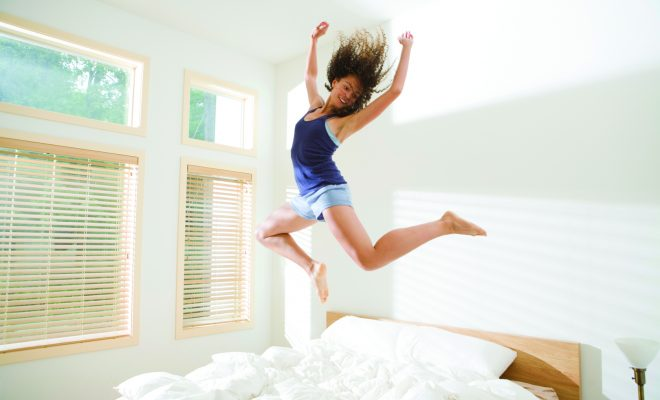 Attractive Young Woman Jumping Energetically on Bed